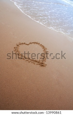 Love on the Beach, tide comes in to wash away heartfelt gesture in the Sand - stock photo