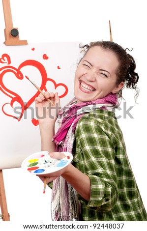 Love or Valentine day - concept image. Beautiful girl with brushes near easel, painting on canvas. - stock photo