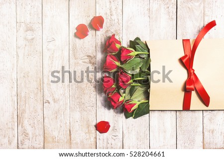Love or valentine's day concept. Red beautiful roses in envelope with red ribbon on a wooden background. Top view