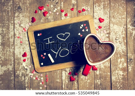 Love or Valentine's Day Concept with Chalkboard, Hearts and Coffee on a old Wooden Background. Top view