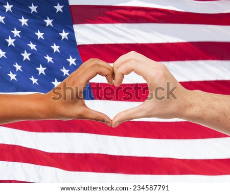 love, patriotism, gesture, peace and people concept - closeup of two hands showing heart shape over american flag - stock photo