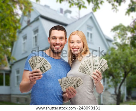 love, people, real estate, home and family concept - smiling couple showing dollar cash money over house background - stock photo