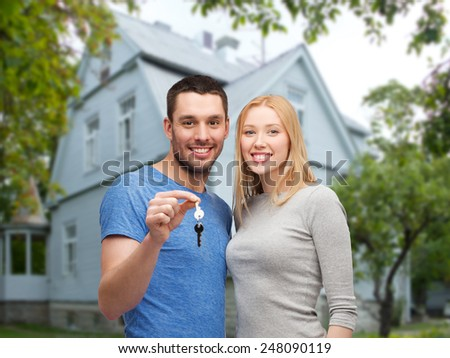 love, people, real estate, home and family concept - smiling couple showing key over house background - stock photo