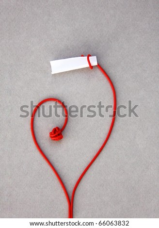 love red note paper: A stalk rolled up around an opened paper forming a heart and showing its contents: ready for your message - stock photo