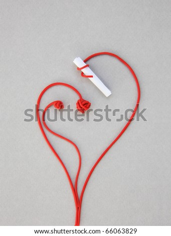 love red paper note: A stalk rolled up around a closed paper keeping its contents secret and drawing a heart