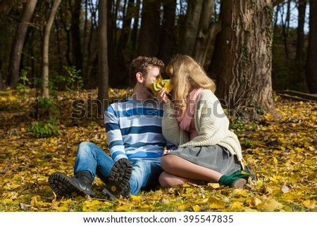 Love relationship dating and people concept - couple hiding behind leaves kissing in autumn park