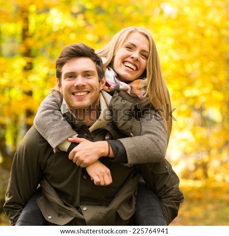 love, relationship, family and people concept - smiling couple having fun in autumn park - stock photo
