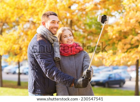 love, relationship, family and people concept - smiling couple hugging and taking selfie with smartphone and monopod in autumn park - stock photo