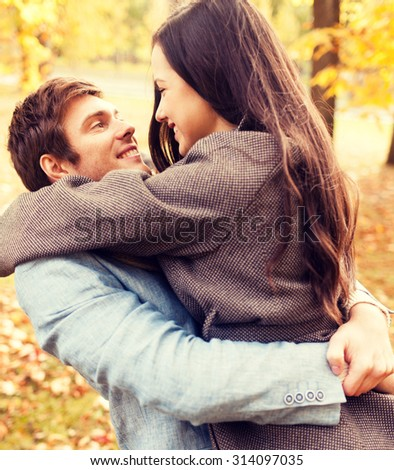 love, relationship, family and people concept - smiling couple hugging in autumn park - stock photo