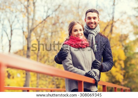 love, relationship, family, season and people concept - smiling couple hugging on bridge in autumn park - stock photo