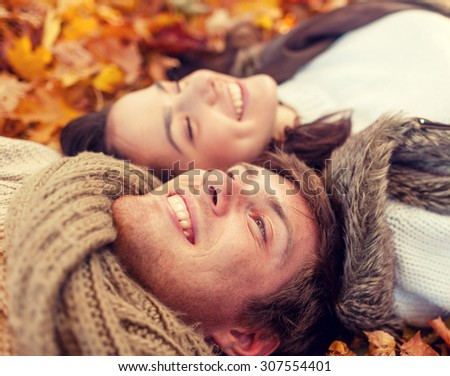 love, relationship, season, family and people concept - close up of smiling couple lying in autumn park - stock photo