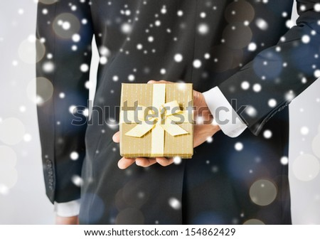 love, romance, holiday, celebration concept - man hiding gift box - stock photo