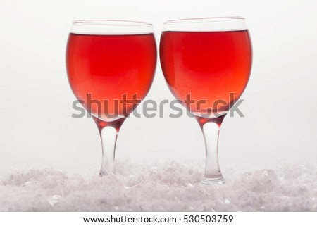 love, romance, holiday, celebration concept - wine glasses on the snow.