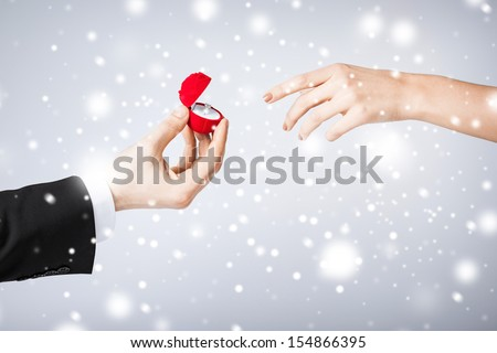 love, romance, marriage, jewelry concept - couple hands with wedding ring and gift box - stock photo