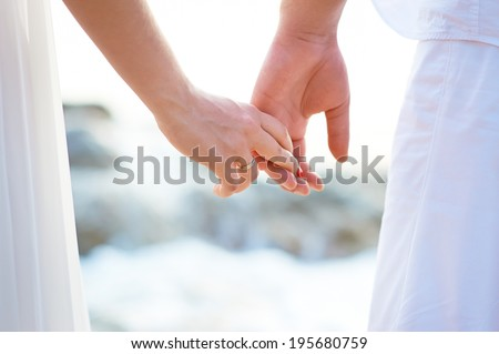 Love - romantic couple holding hands on a beach in sunset. - stock photo