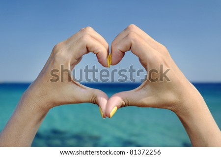 Love sea and vacation hands heart gesture