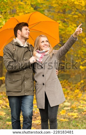 love, season, family, gesture and people concept - smiling couple with umbrella walking and pointing finger in autumn park - stock photo