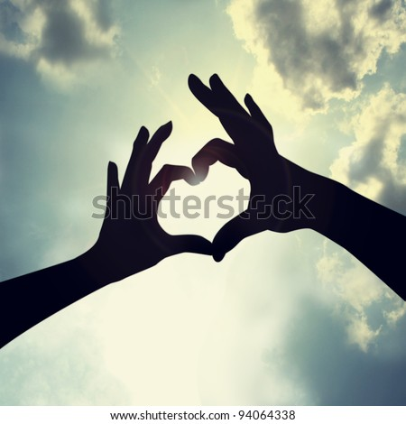love shape hand silhouette in sky - stock photo