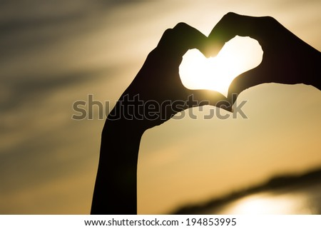 Love sign. Heart symbol by hand silhouette in sunset sky. - stock photo