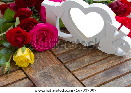 love sign with  multicolored roses on wooden table - copy space - stock photo