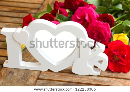 love sign with  roses on wooden table - copy space - stock photo