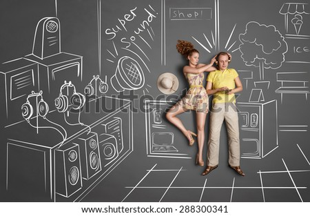 Love story concept of a romantic couple against chalk drawings background. Male listening to the music in the headphones and surfing internet, female trying to gain his attention. - stock photo