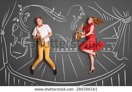Love story concept of a romantic couple against chalk drawings background. Musician couple playing serenade on saxophone on stage. - stock photo