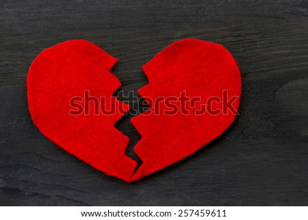 Love story concept. Top view of red broken heart shape on wooden background