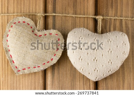 Love story concept. Two soft hearts on wooden background - stock photo