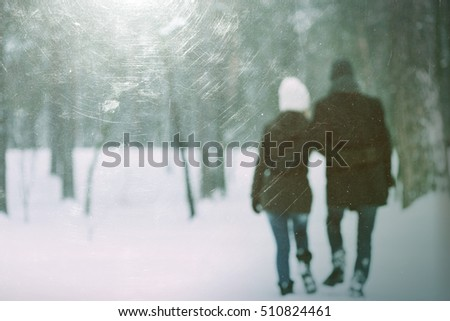 Love story in park. Couple walking outdoors embracing. Photo in defocusing. Color toning. The effect of old photos from scuffs and scratches