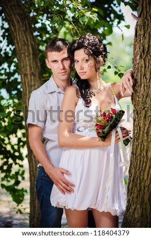 Love story of happy couple. Groom and Bride sitting on a bench in a park. wedding dress. Bridal wedding bouquet of flowers. feelings, relations, passion - stock photo