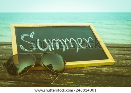 love summer decorate with eyeglasses and  chalkboard on wooden floor on the blue sea. - stock photo