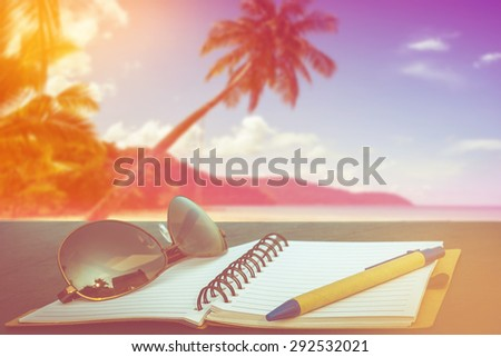 love summer decorate with eyeglasses and note book on wooden floor on tropical beach party on day noon light background,vintage filter color tone. - stock photo