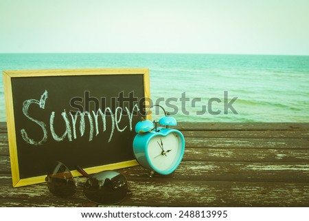 love summer time decorate with eyeglasses and  chalkboard on wooden floor on the blue sea. - stock photo