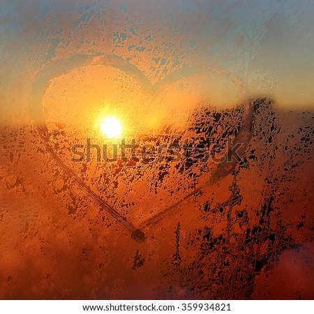 Love symbol drawn on the frozen winter window - stock photo