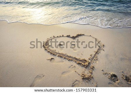 Love symbol. Heart written on sand of a beautiful beach in Emirates. - stock photo
