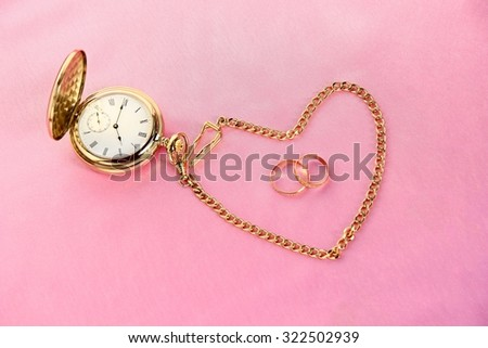 Love takes time - golden pocket watch and rings on pink background.