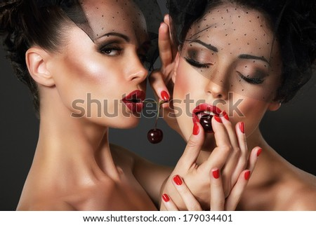 Love. Temptation. Pair of Sexy Women Eating Cherry Berries  - stock photo