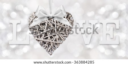love text with heart of woven wood with ribbon bow on silver blurred light background - stock photo