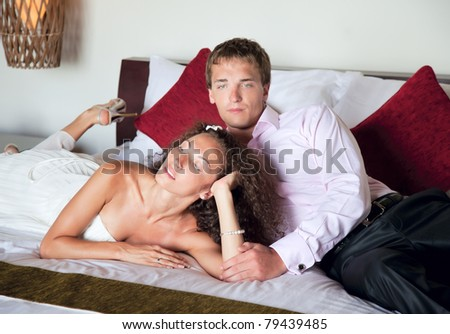 Love the happy couple in bed holding each other's hands - stock photo