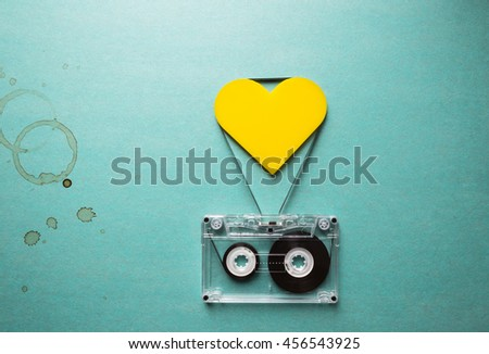 love to music, audio cassette with yellow heart and coffee stains on a green background