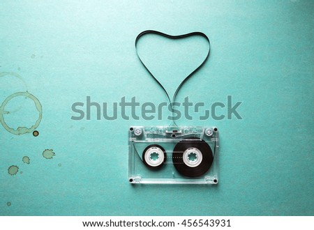love to music, twisted audio tape in the shape of a heart and coffee stains on a green background
