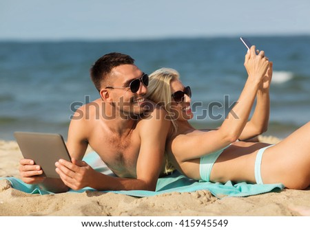 love, travel, tourism, technology and people concept - happy couple on vacation with tablet pc computer and smartphone sunbathing on summer beach - stock photo