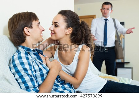 Love triangle: adult husband, positive wife and lover at domestic interior - stock photo