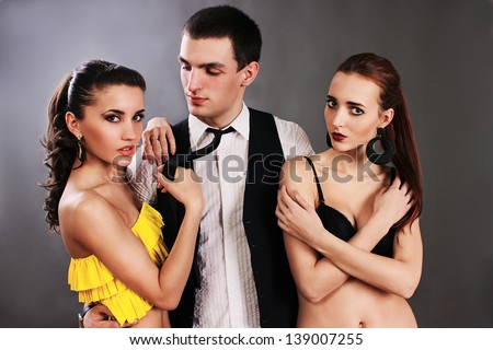 Love triangle of two women and one mane. One man passion of love and hate. Infatuation love. Mistress and betrayal within the family. A man makes a choice between two women. Choice before wedding. - stock photo