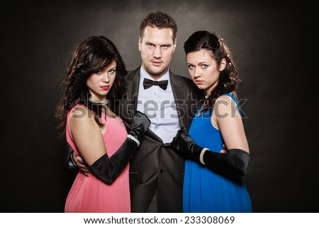 Love triangle. Portrait of two women and one man wearing elegant clothes on black. Mistress and betrayal within the family. Choice before wedding. Luxury party. - stock photo