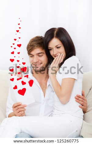love valentine day couple reading valentine's greeting card, note, letter with red heart, happy smile, hug, sitting on couch, concept hearts flying around - stock photo