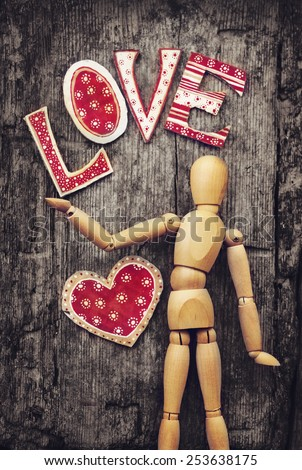 Love valentines day background, wooden man holding red heart on wooden table background - stock photo