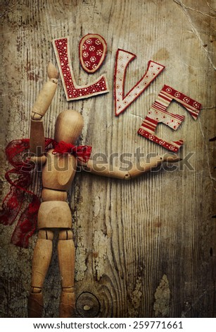 Love valentines day background, wooden man with red bow on his neck dancing, holding love on wooden table background - stock photo