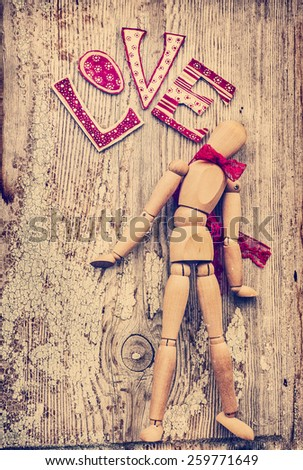 Love valentines day background, wooden man with red bow on his neck dancing, holding red heart on wooden table background - stock photo